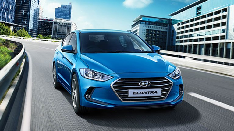 3D image of a Hyundai Elantra driving in a city with glass buildings in the background
