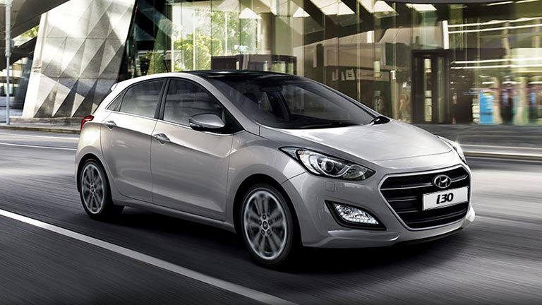 Hyundai i30, the sports hatchback driving in front of a hotel gate