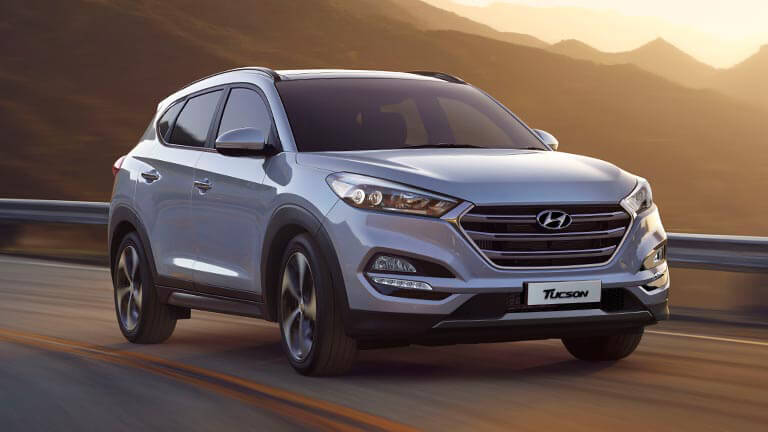 Silver Hyundai Tucson gushing down valley road on sunset with beautiful mountains in the background