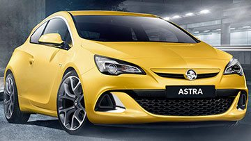 The two door Holden Astra PJ in yellow inside a stadium with bright focus lights