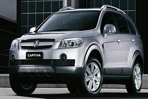 Front angled view of the Holden Captiva, a full sized SUV parked outside an Industrial Park