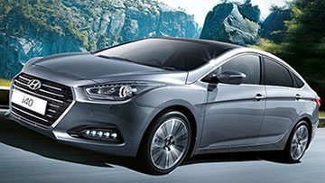 Grey hyundai i40 VF2 pictured speeding down the highway with beautiful mountains in the background