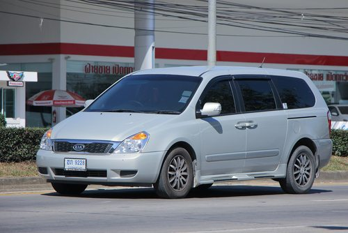 Light grey Kia Carnival VQ outside a gas station