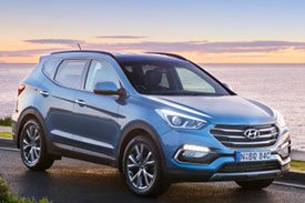 Blue Hyundai Santa FE DM pictured during a sunset near a river with a scenic view