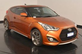 An orange Hyundai Veloster hatchback model number FS2, at the Hyundai's auto show