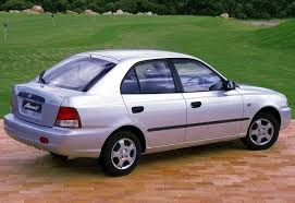 Read view of a classic version of the popular Hyundai Accent, parked on a walking patch in a garden