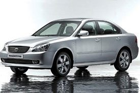 Side view of Kia Magentis MG, a beautiful sedan parked on a wet reflecting road