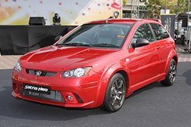 Red Proton Satria Neo at an auto show on an open road