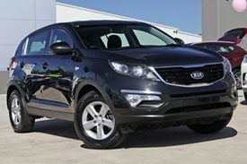 Metallic black Kia Sportage SL Series II parked outside the Kia showroom