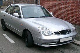 Daewoo Leganza, the classic sedan parked outside with a red bricked wall in the background
