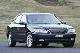 Black Hyundai Grandeur, classic sedan parked on a country road