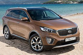 Brown Kia Sorento UM parked on a beach with beautiful blue water in the background