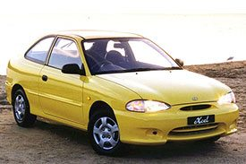 Classic two door yellow Hyundai Excel, model number X3, pictured on a hilly road at sunset