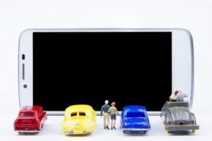 Miniature cars lined up against a phone screen